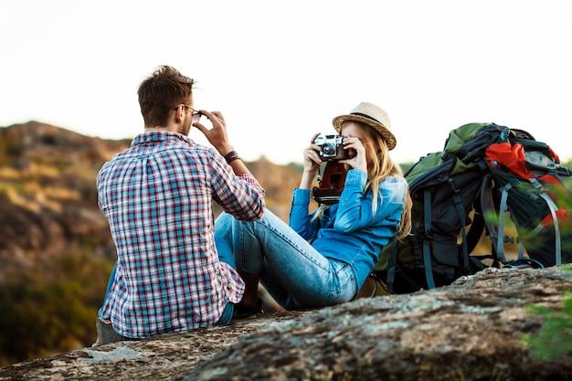 Fotógrafo feminino loiro lindo tirando foto do namorado, fundo do canyon