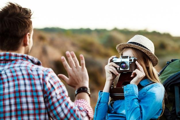 Fotógrafo feminino loiro lindo tirando foto do namorado