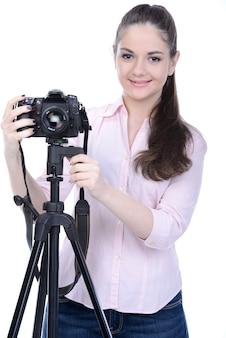 Fotógrafo feminino segurando uma câmera profissional.