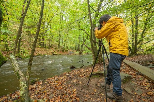 Fotógrafo feminino tira fotos de uma bela vista do rio e da floresta., longa exposição