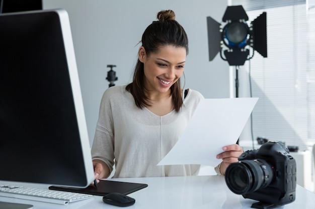 Fotógrafo feminino usando tablet gráfico na mesa