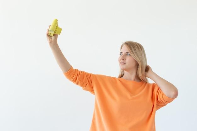 Fotógrafo, hobby e conceito de lazer - jovem mulher loira com câmera retro na parede branca