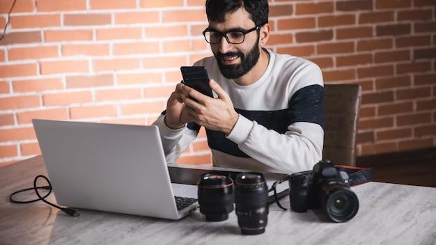 Fotógrafo homem mão telefone com lente na mesa