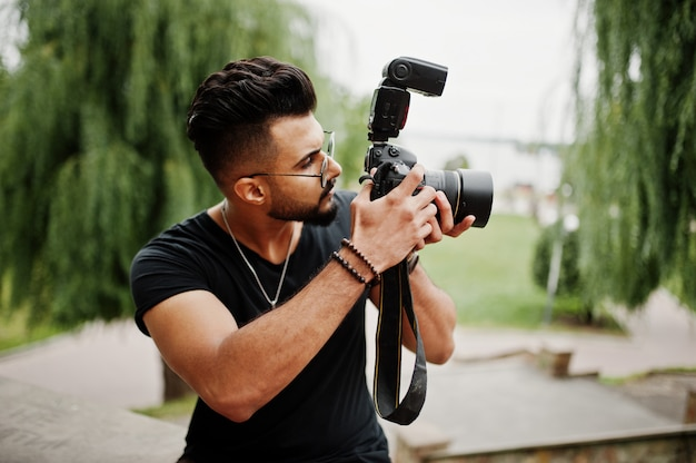 Fotógrafo impressionante lindo homem de barba alta de óculos e camiseta preta com câmera profissional nas mãos