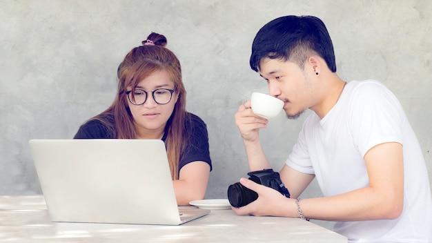 Fotógrafo jovem asiático, trabalhando com o laptop no fundo cinza no studio