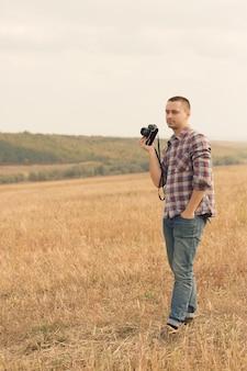 Fotógrafo masculino atraente ao ar livre ao pôr do sol