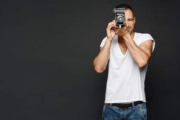 Fotógrafo masculino bonito, um repórter com câmera retro, preparando-se para tirar uma foto, isolada na parede escura