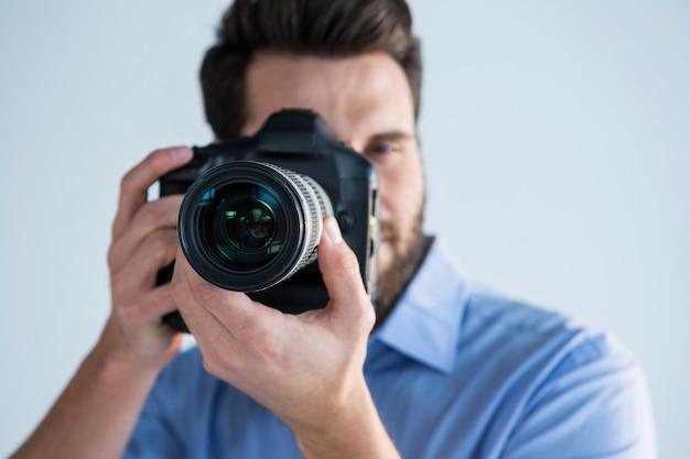Fotógrafo masculino com câmera digital em estúdio