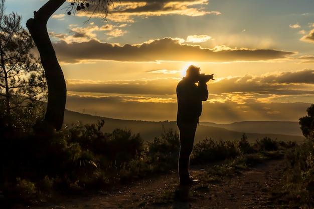 Fotógrafo masculino fotografando o pôr do sol em um dia com nuvens.
