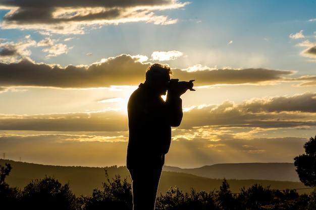 Fotógrafo masculino fotografando o pôr do sol em um dia com nuvens. Foto Premium