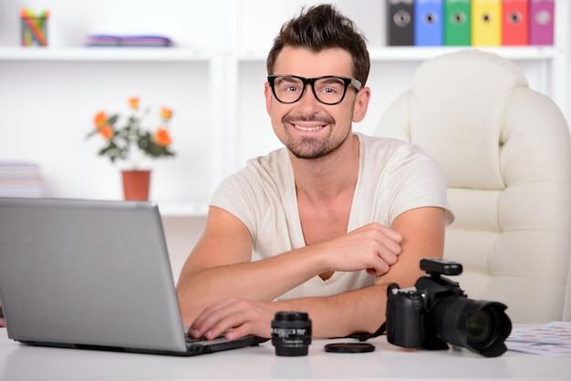 Fotógrafo masculino novo que trabalha em seu escritório.