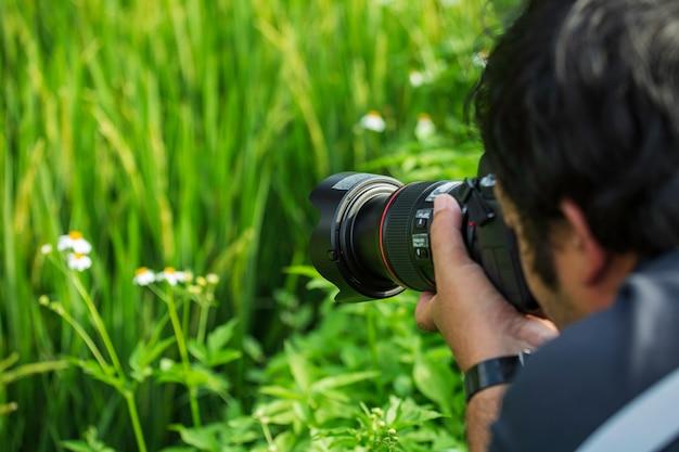 Fotógrafo masculino tirando fotos de flores brancas lindo arrozal verde