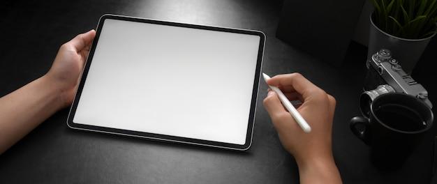Fotógrafo masculino usando laptop de tela em branco com caneta stylus