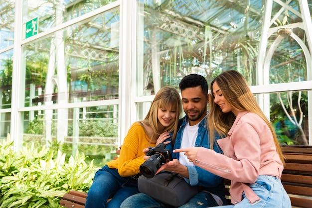 Fotógrafo mostra seu trabalho em sua câmera para duas meninas sentadas em um banco