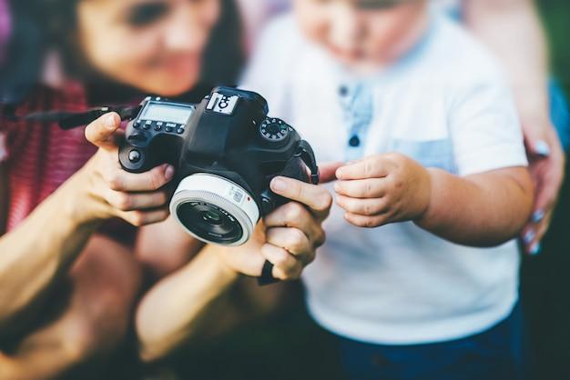 Fotógrafo mostrando fotos de criança pequena na câmera