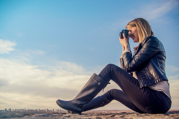 Fotógrafo mulher garota está segurando câmera dslr tirando fotografias. jovem sorridente usando uma câmera para tirar fotos ao ar livre