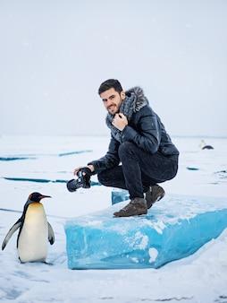 Fotógrafo no ártico com fotos de um pinguim
