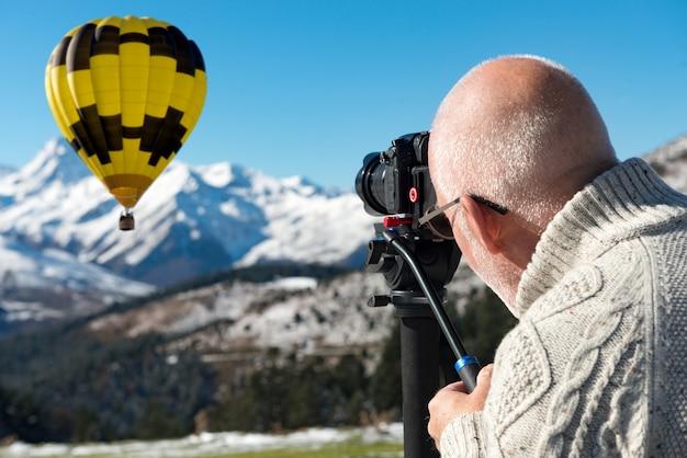 Fotógrafo no topo da montanha com balão de ar quente