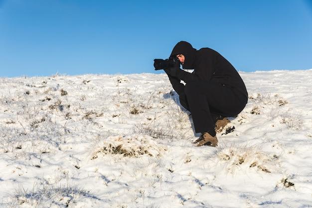 Fotógrafo no trabalho na neve no inverno