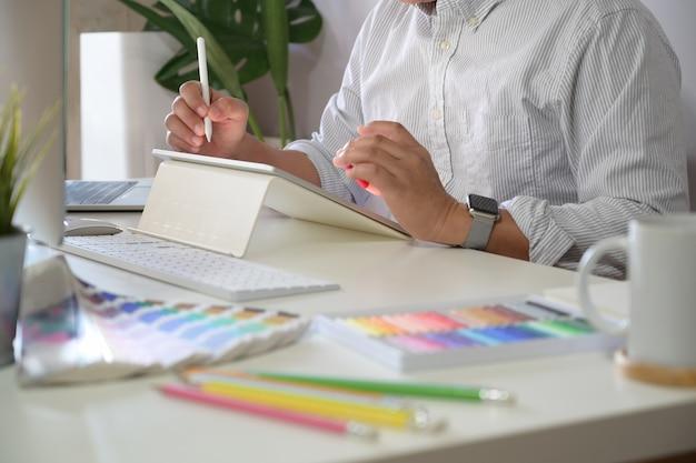 Fotógrafo novo e designer gráfico no trabalho no escritório do estúdio.