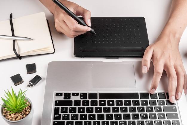 Fotógrafo ou designer usando laptop e tablet para editar.
