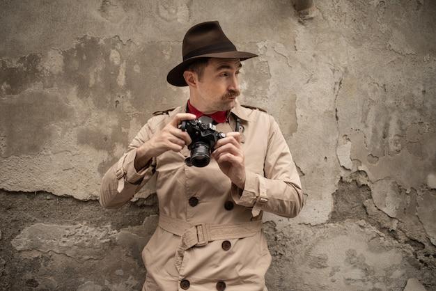 Fotógrafo paparazzo usando a câmera em uma rua da cidade