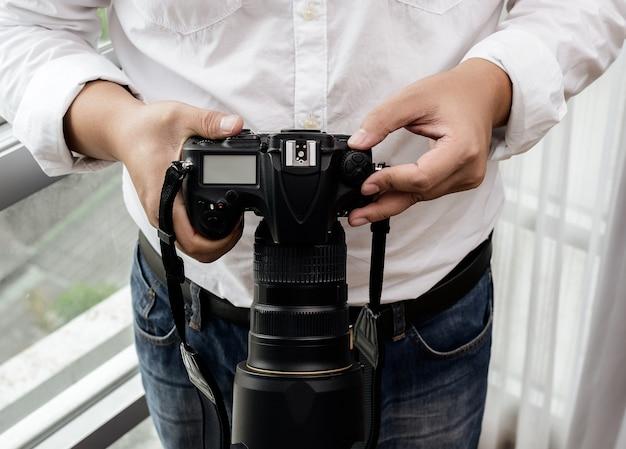 Fotógrafo profissional ajusta a câmera antes de fotografar