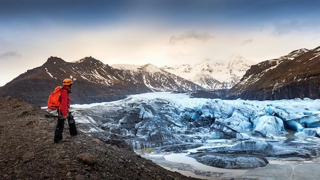 Fotógrafo profissional com câmera e tripé no inverno. fotógrafo profissional olhando para uma geleira na islândia.