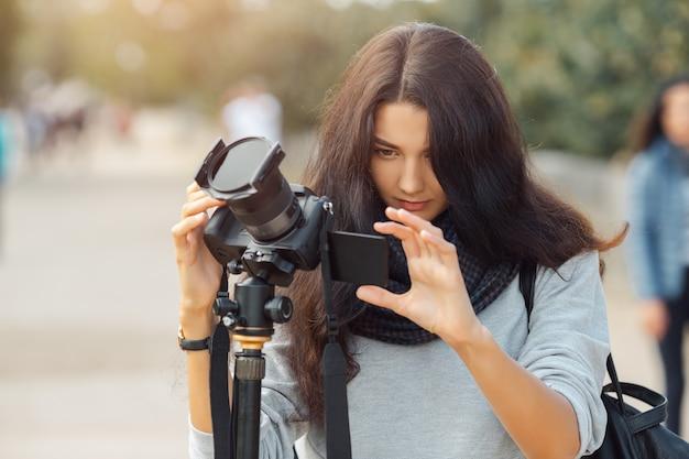 Fotógrafo profissional de mulher tirando fotos de paisagens com câmera dslr e tripé ao ar livre.