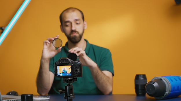 Fotógrafo profissional falando sobre o efeito dos filtros nd na imagem para seu vlog. revisão do filtro nd variável, equipamento da câmera e vídeo do equipamento. ceator influenciador estrela de mídia social distribuindo online cont