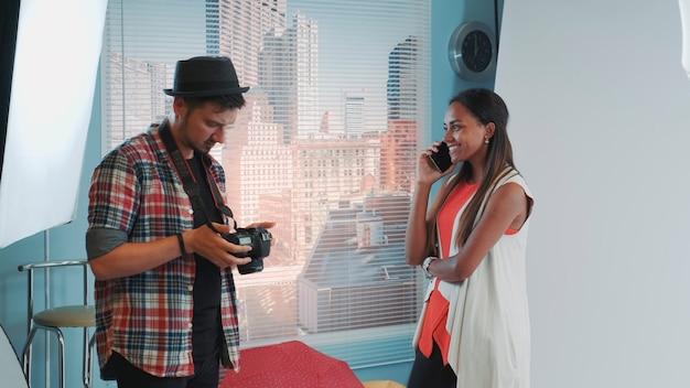 Fotógrafo profissional pedindo a modelo para parar de falar no smartphone e continuar trabalhando mulher negra ...
