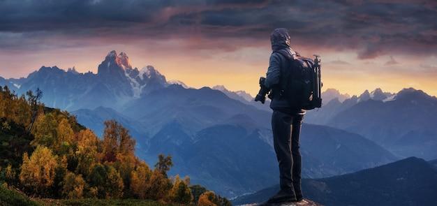 Fotógrafo profissional tira fotos com a câmera grande no pico da rocha