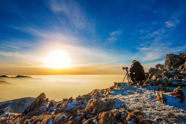 Fotógrafo profissional tira fotos com a câmera no tripé no pico rochoso ao pôr do sol
