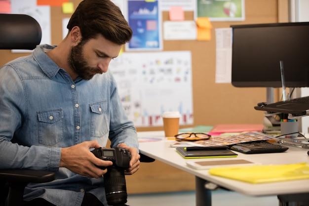 Fotógrafo profissional usando câmera em escritório criativo