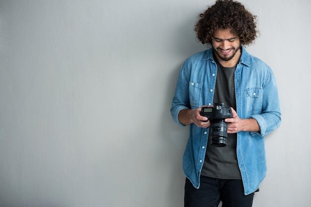 Fotógrafo revendo fotos capturadas em sua câmera digital