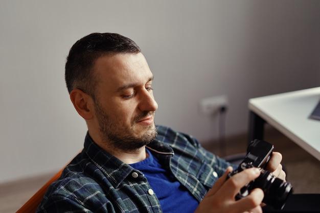 Fotógrafo segurar câmera digital, olhando para a tela branca