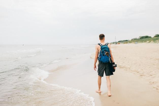 Fotógrafo solitário com uma câmera na mão, caminhando na praia