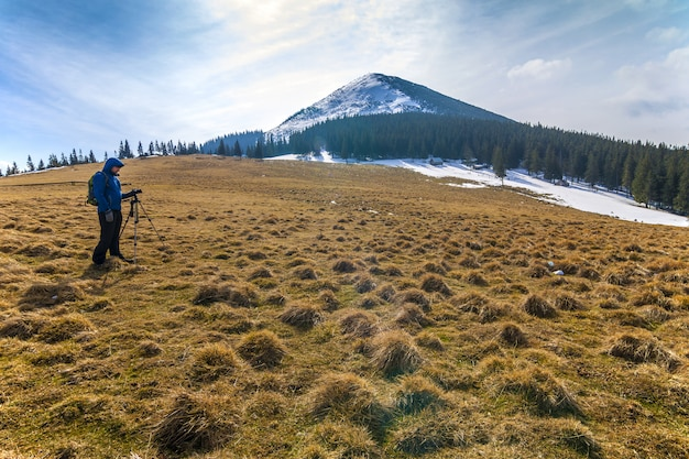 Fotógrafo solitário nas montanhas com uma câmera
