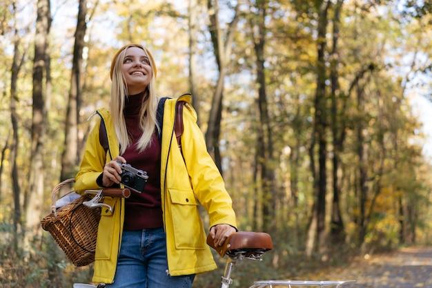 Fotógrafo sorridente segurando a câmera planejando tirar fotos na floresta de outono viagem de inspiração
