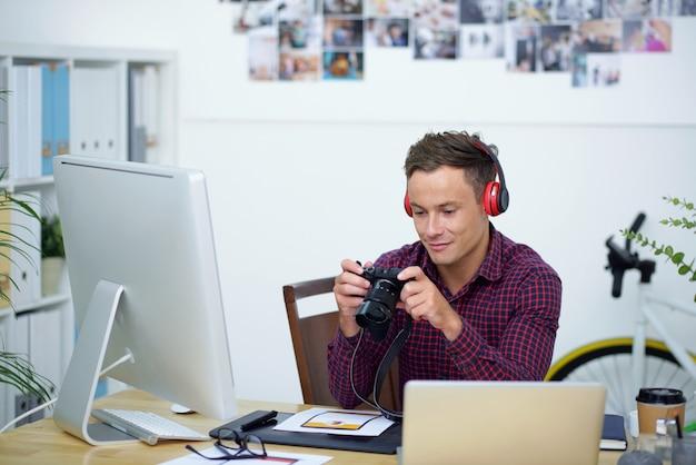 Fotógrafo sorridente sentado na mesa do escritório e olhando as fotos que fez da câmera digital no dia anterior