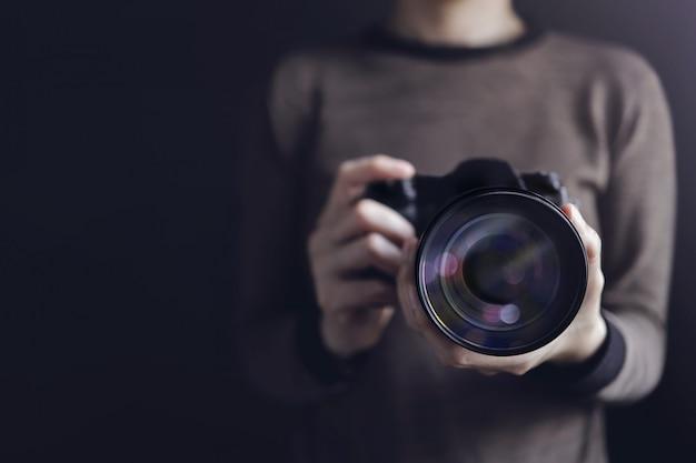 Fotógrafo tirando auto-retrato. mulher usando a câmera para tirar foto.