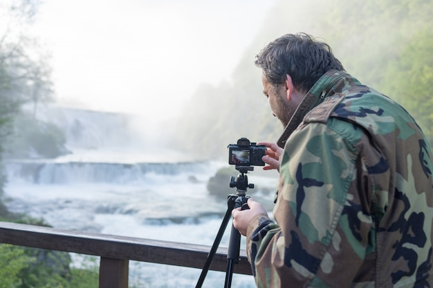 Fotógrafo tirando foto de cachoeira no início da manhã