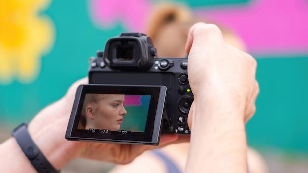 Fotógrafo tirando foto de uma jovem loira em roupas esportivas em treinamento ao ar livre, plano de fundo multicolorido