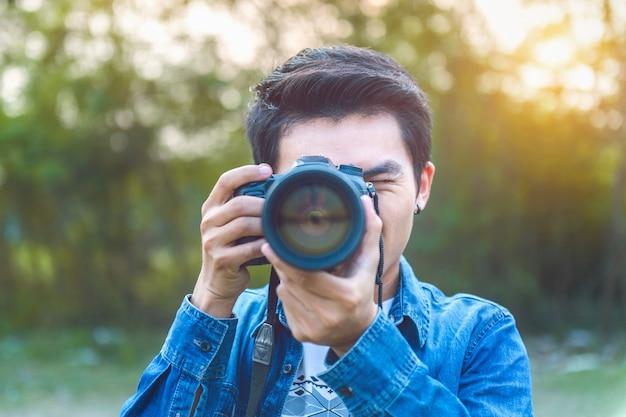 Fotógrafo tirando fotos com câmera digital. tom vintage.