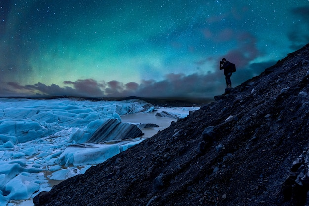 Fotógrafo tirando fotos da geleira e da aurora boreal na islândia