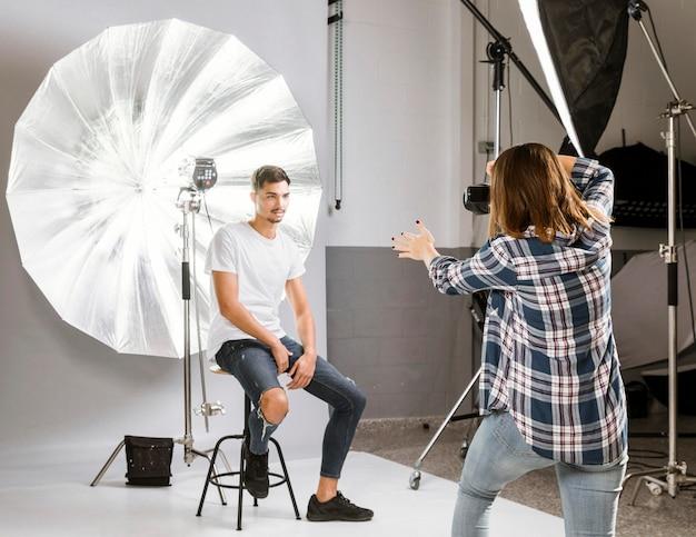 Fotógrafo tirando fotos do modelo bonito