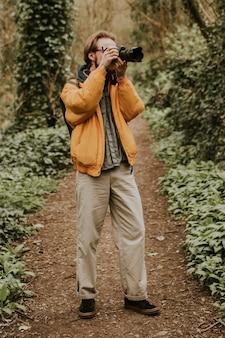 Fotógrafo tirando fotos na floresta ao ar livre