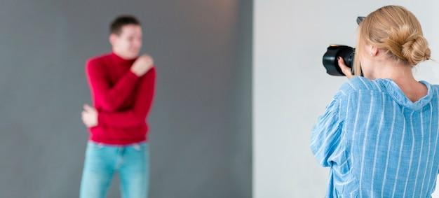 Fotógrafo tirando fotos para o homem de camisa vermelha