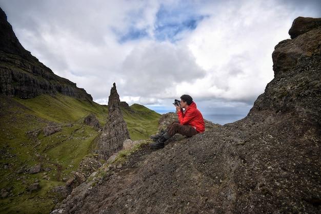 Fotógrafo tirando fotos sentado em uma pedra de uma montanha