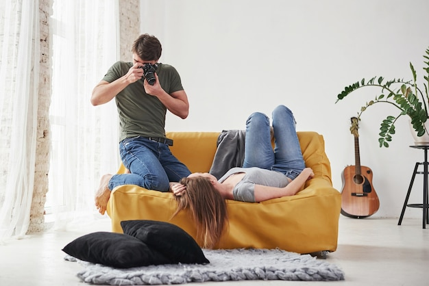 Fotógrafo tirando uma foto da jovem que estava deitada no sofá branco.
